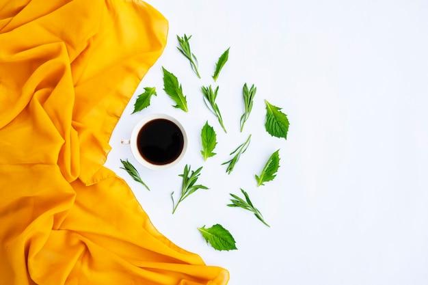 Minimalistisches konzept. gelber schal, kaffee und grüne blätter auf weißem hintergrund. herbst. flache lage, ansicht von oben, kopienraum