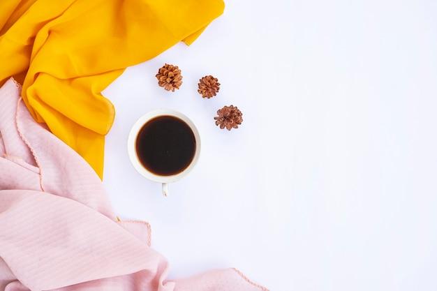 Minimalistisches konzept. kaffee, kiefernblume, gelber schal, brauner schal auf weißem hintergrund. herbst, herbstkonzept. flache lage, ansicht von oben, kopienraum