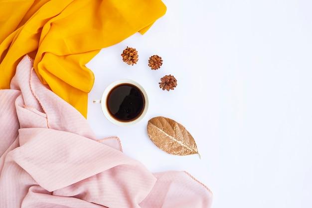 Minimalistisches konzept. kaffee, trockene blätter, kiefernblume, gelber schal auf weißem hintergrund. herbst, herbstkonzept. flache lage, ansicht von oben, kopienraum