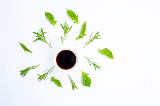 Minimalistisches konzept. kaffee und grüne blätter auf weißem hintergrund. herbst. flache lage, ansicht von oben, kopienraum