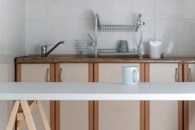 Minimalistisches küchendesign in hellen farben. modernes kücheninterieur. tasse auf dem tisch.