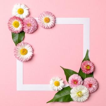 Minimalistisches layout aus papierrahmenrand und zarten frühlingsblumen auf pastellrosa hintergrund.