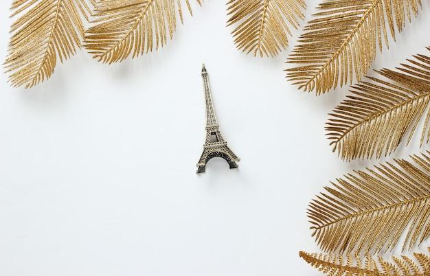 Minimalistisches mode-stillleben. eiffelturmfigur unter dekorativen goldenen palmblättern auf einem weißen hintergrund. draufsicht