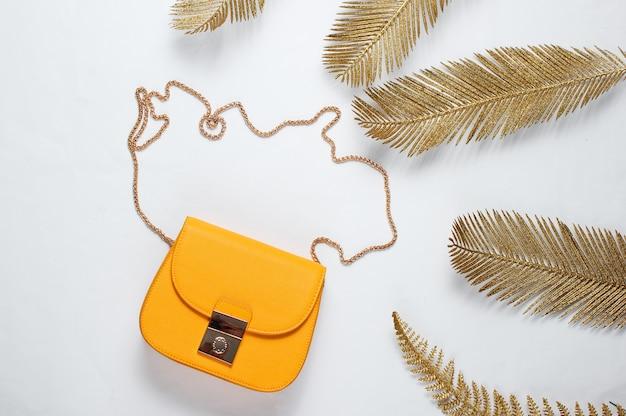 Minimalistisches mode-stillleben. leder gelbe tasche unter dekorativen goldenen palmblättern auf einem weißen hintergrund. draufsicht