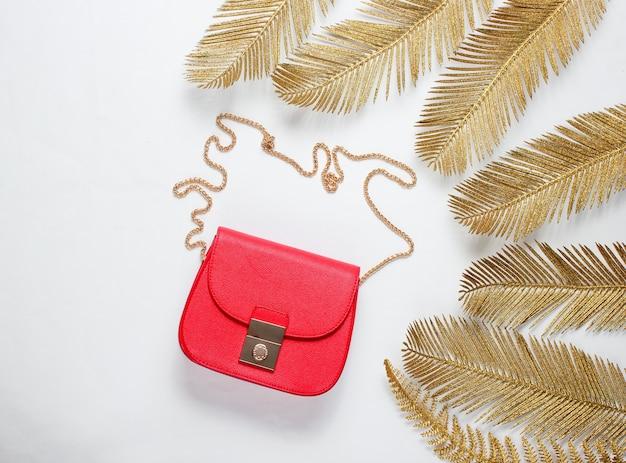 Minimalistisches mode-stillleben. rote ledertasche unter dekorativen goldenen palmblättern auf weißem hintergrund. draufsicht