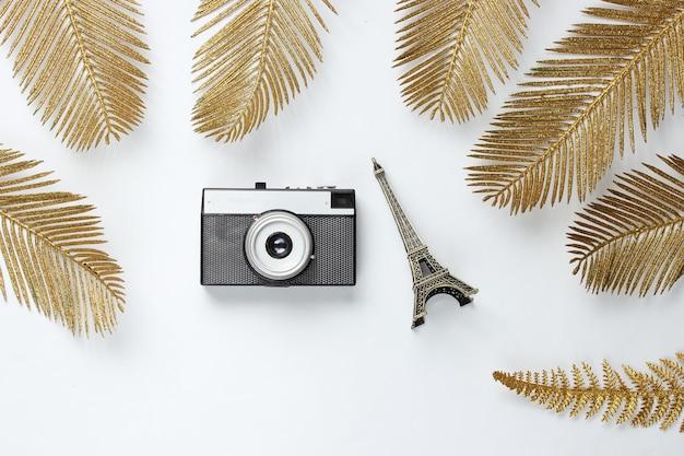 Minimalistisches reisestillleben. eiffelturmfigur, retro-kamera unter dekorativen goldenen palmblättern auf einem weißen hintergrund. draufsicht