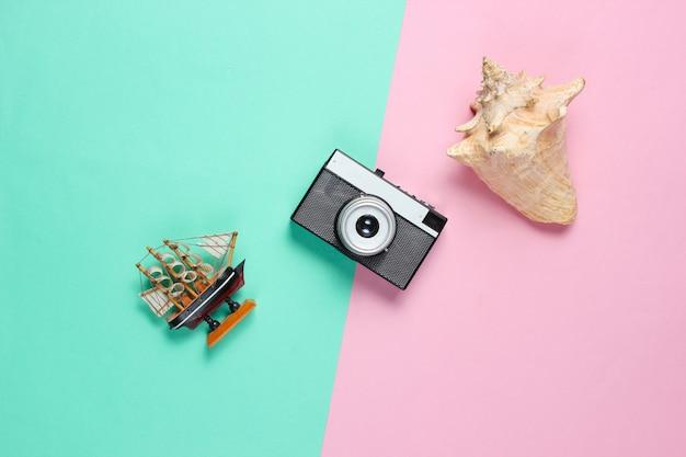 Minimalistisches reisestillleben. muscheln, retro-kamera, dekorativer blauer rosa pastellhintergrund des schiffs.