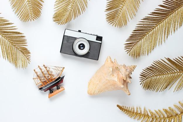 Minimalistisches reisestillleben. muscheln, retro-kamera unter dekorativen goldenen palmblättern auf einem weißen hintergrund. draufsicht