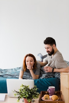 Minimalistisches schlafzimmerdesign und paar mit laptop