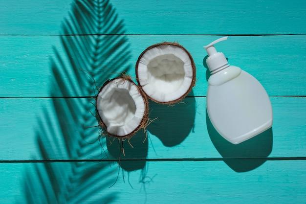 Minimalistisches schönheitsstillleben. zwei hälften gehackte kokosnuss und weiße flasche sahne mit schatten von palmblättern auf blauem hölzernem hintergrund. kreatives modekonzept.