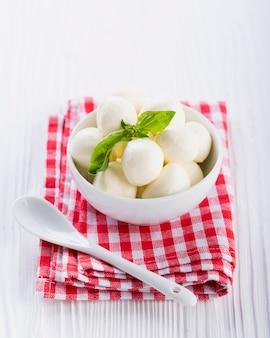 Minimozzarella in der schüssel mit basilikum