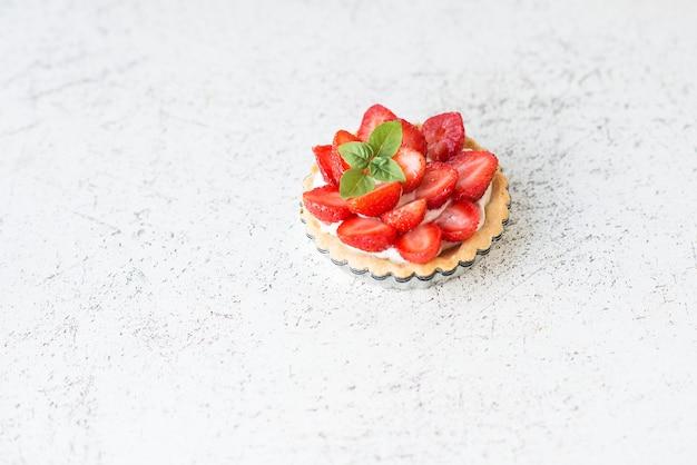 Minitarte mit erdbeerbeeren auf weiß