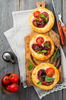 Minitörtchen mit getrocknetem fleisch, tomaten, ricotta, thymian, basilikum und oliven auf einem alten holz