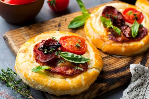 Minitörtchen mit getrocknetem fleisch, tomaten, ricotta, thymian, basilikum und oliven auf grauem beton. rustikaler stil