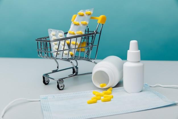 Minitrolley mit medizinischen gütern auf blauem hintergrund. online-shopping-konzept.