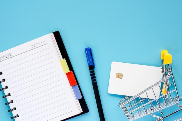 Miniwarenkorb oder laufkatze mit leerer kreditchipkarte, gewundenem notizbuch und stift auf blauem hintergrund