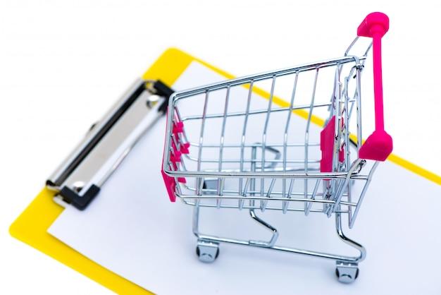 Miniwarenkorb oder supermarktlaufkatze auf klemmbrett mit leerem weißbuchblatt
