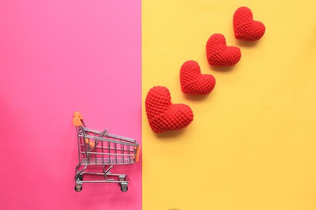 Miniwarenkorb und rotes handgemachtes häkelarbeitherz auf gelbem und rosa hintergrund für valentinstag