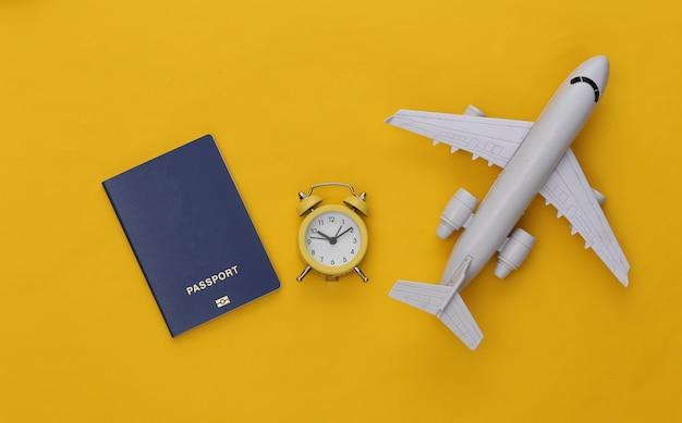 Miniwecker und flugzeug, reisepass auf gelbem hintergrund. zeit zu reisen.