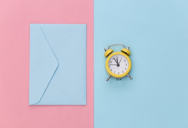 Miniwecker und umschlag auf rosa blauem pastellhintergrund.