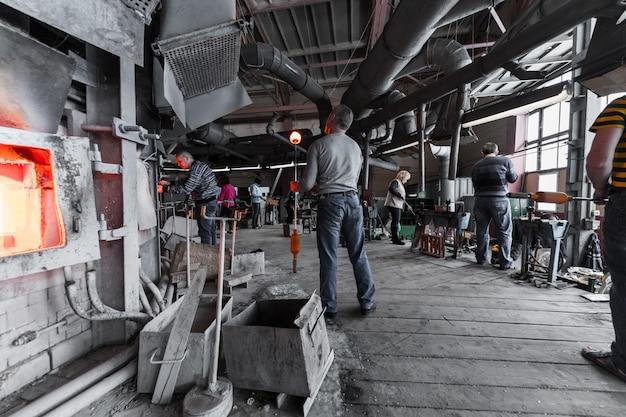 Minsk, weißrussland - 1. februar 2018: glasproduktionsarbeiter, der mit industrieausrüstung auf fabrik arbeitet