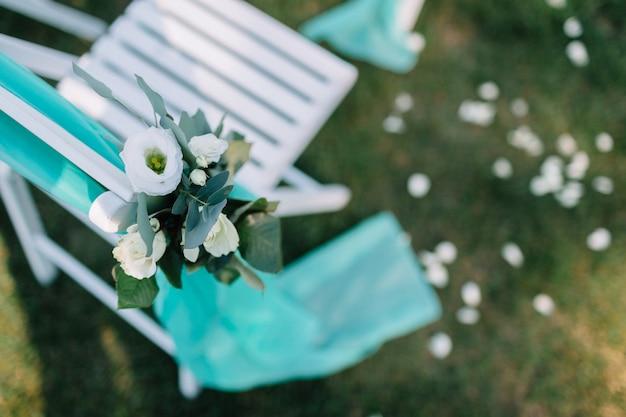 Mint tuch hängt vom weißen stuhl auf dem rasen