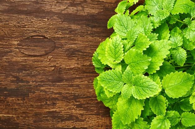 Minzblätter auf einem hölzernen hintergrund. melissa