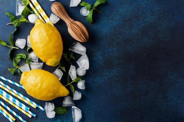 Minzblätter, frische zitrone und honig liegend halten netz einkaufen baumwolltasche auf blauem beton.