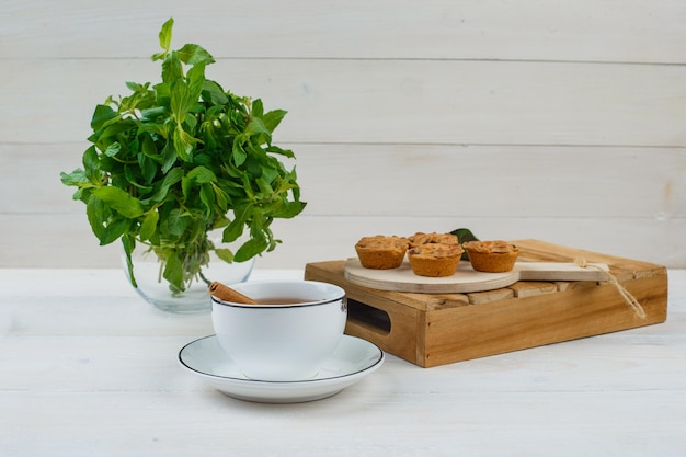 Minze in einem einmachglas mit einer tasse tee, kuchen auf schneidebrett