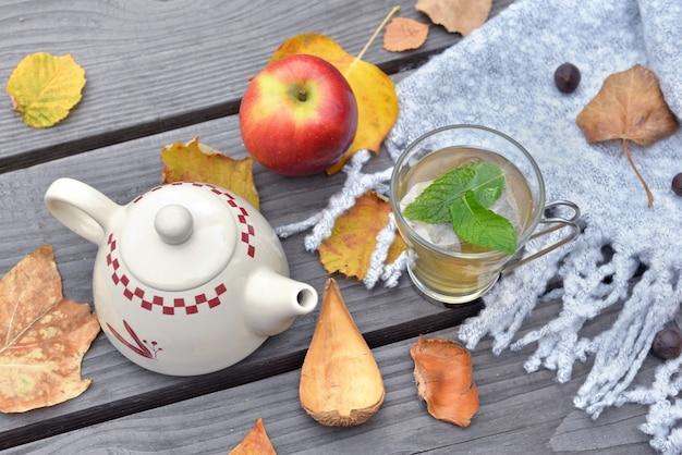 Minze tasse tee auf einem holztisch im garten mit teekanne zwischen herbstlichem blatt und rotem apfel auf wollschal