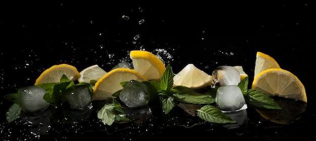 Minze, zitrone und eis in wasserspritzern auf dunklem hintergrund