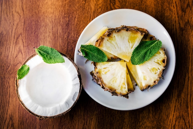 Minzeblätter liegen auf ananas und kokosnuss