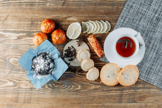 Minztee in einer tasse mit geschnittener zitrone, keksen, nelken draufsicht auf holztisch