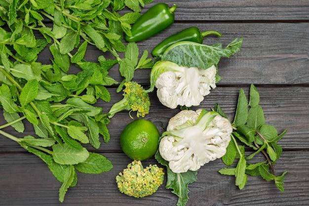 Minzzweige, brokkoli und blumenkohl. limette und grüne paprika auf dem tisch. holz hintergrund. flach legen