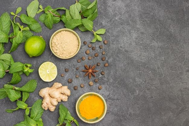Minzzweige, limette, rohe ingwerwurzel sowie trockener ingwer und kurkuma in schalen