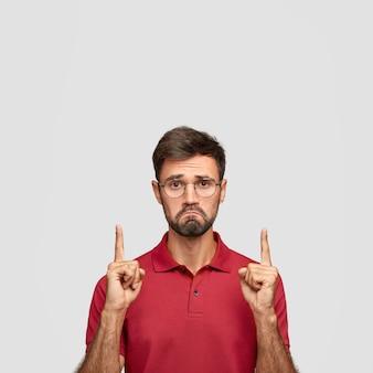 Mir gefällt nicht, was ich sehe. hübscher mann mit stoppeln hebt beide zeigefinger und zeigt nach oben