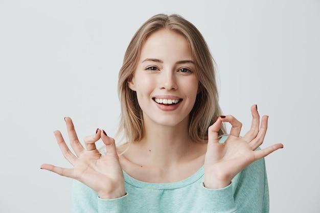 Mir geht es prächtig. frohes glückliches junges blondes weibchen im blauen pullover, das breit lächelt und mit beiden händen ok geste macht, sich über guten tag, lebensziele, erfolge freut. körpersprache. freude und frohsinn.