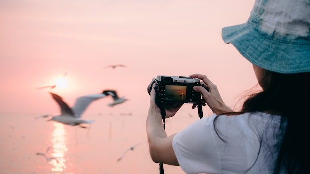 Mirrorless-kamera des frauenabnutzungshutgebrauches, die seemöwenfoto im sonnenuntergang macht.