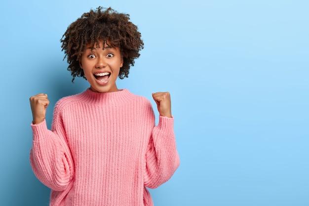 Mirthful frau mit einem afro, der in einem rosa pullover aufwirft