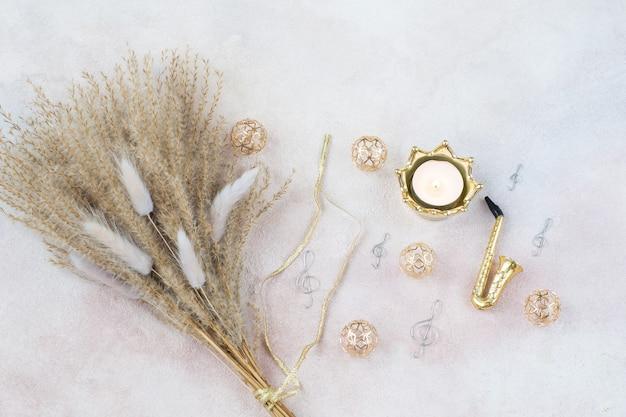 Miscanthus bouquet, saxophon, violinschlüssel, kerze und golddekor