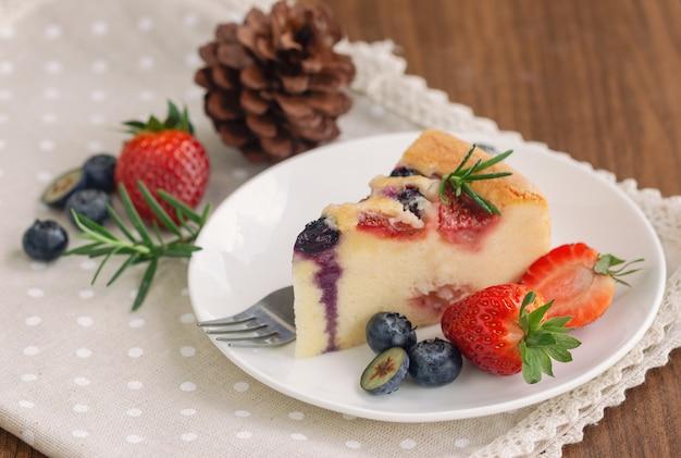 Mischbeerenbutterkuchen mit frischen blaubeeren und erdbeeren auf weißer platte setzte an hölzerne tabelle in seitenansichtkopienraum.