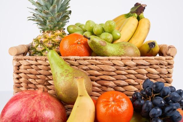 Mischen sie eine vielzahl von frischen saftigen bunten exotischen tropischen früchten im korb auf weißem hintergrund
