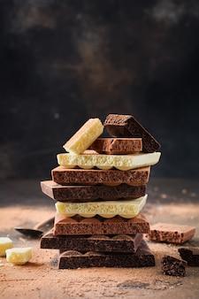 Mischen sie einen stapel bitterer, milchiger und weißer poröser luftiger schokolade auf einer dunklen alten oberfläche