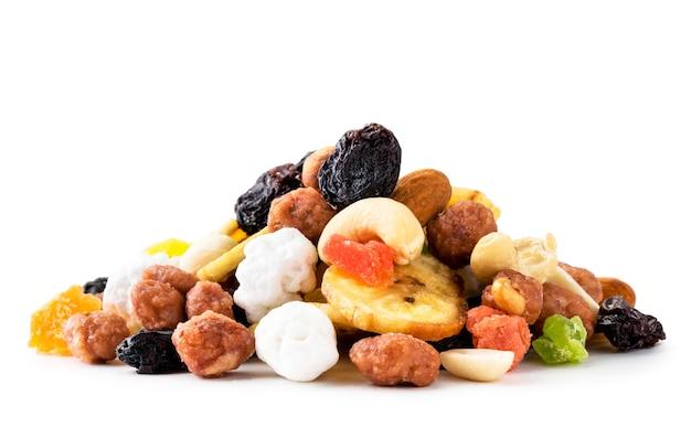 Mischen sie einen stapel getrockneter früchte mit nüssen auf einem weißen hintergrund. isoliert