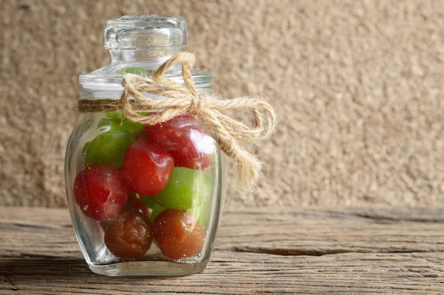 Mischen sie essiggurkenkirschfrucht in der glasflasche auf holztisch