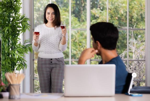 Mischen sie familienliebhaber, kaukasischen ehemann und asiatische ehefrauen, einen mann, der am schreibtisch mit laptop-computer arbeitet, und eine frau, die ein paar rotweingläser zum feiern und entspannen nimmt. konzept der liebe und fürsorge zu hause