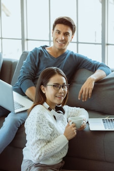 Mischen sie familienliebhaber, kaukasischer ehemann und asiatische frau, die im wohnzimmer sitzen und über laptop-computer auf dem sofa in einfachen entspannungsgesten arbeiten. konzept der arbeit zu hause und des neuen normalen modernen lebensstils.