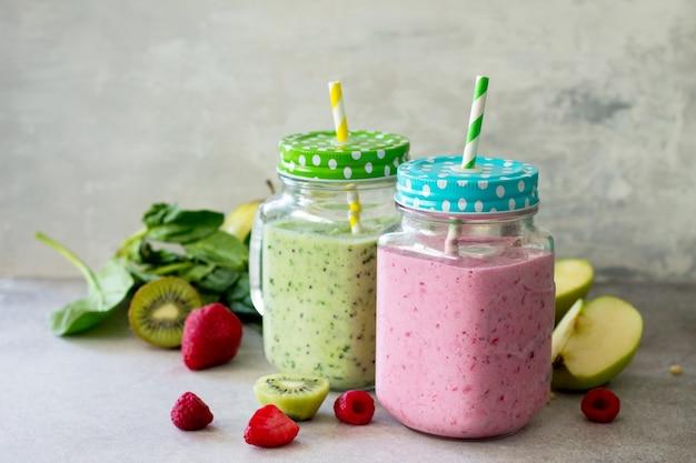 Mischen sie frischen fruchtsmoothie und grüne smoothies auf einem grauen stein oder schiefer
