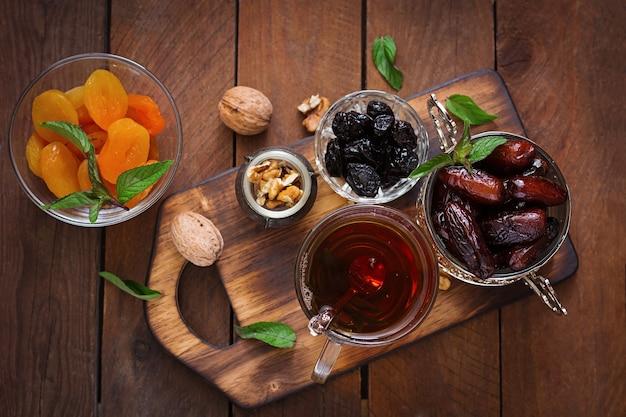 Mischen sie getrocknete früchte (dattelpalme früchte, pflaumen, getrocknete aprikosen, rosinen) und nüsse und traditionellen arabischen tee. ramadan (ramazan) essen. draufsicht