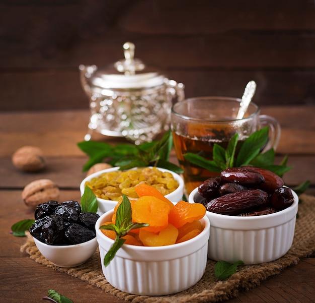 Mischen sie getrocknete früchte (dattelpalme früchte, pflaumen, getrocknete aprikosen, rosinen) und nüsse und traditionellen arabischen tee. ramadan (ramazan) essen.